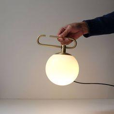 Lampe à poser de la collection Yanzi d'Artemide, composé d'une structure tubulaire en laiton doré agrémentée d'un diffuseur sphérique en verre opalin ; ce modèle est équipé d'un cordon d'alim...