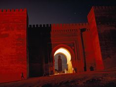 Moroccan Mosque  Photograph by Thomas J. Abercrombie    A glowing keyhole arch and dusty-red walls frame the minaret of Al Berdain Mosque in Meknès, Morocco. The arch's lighting also suggests a crescent moon, one of Islam's traditional symbols.