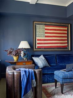 In a Manhattan apartment decorated by Phoebe Howard, study walls painted Benjamin Moore's Newburyport Blue set off a striking Civil War-era flag. The plaid ottoman stands in for a typical coffee table.