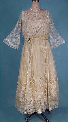 1915 R.H. Stearns & Co., Boston Ecru Embroidered Lace Wedding Dress. Embroidered nouveau design on material appliques on skirt and bodice. Rare stylized lace on skirt hem and yoke. Floral lace net bell sleeves.