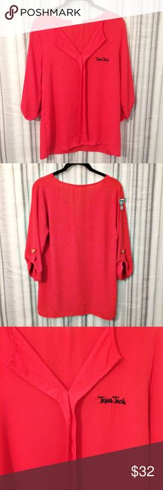 """Texas Tech Red Popover Top Tab Sleeve Size Medium Texas Tech Red Raiders top women's size medium  V neck popover top with ruffle front detail and tab sleeves with adorable buttons  Texas Tech emblazoned on the front and the logo sewn on the shoulder  One spot of rubbing on one button Long tunic style Excellent condition, no signs of wear or damage  18"""" pit to pit  26.5"""" shoulder to hem Everly Tops Blouses"""