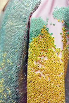 This is attributed to Aisling Farrell, but I believe it's really the work of Maia Bergman as part of her fashion studies finals collection.  This glorious texture uses plastic beads in delicious colors.  Find more at http://1granary.com/central-saint-martins-fashion/ba-final-collections/maia-bergman/