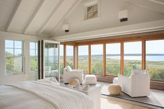 Upstairs in the master bedroom, a wall of windows opens to a screened porch. — archdigest.com