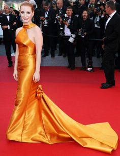 JESSICA CHASTAIN in a citrus colored Armani Privé halter gown with train at the 70th anniversary celebration of the festival - Cannes 2017