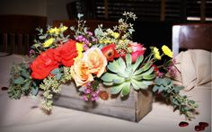Succulent roots are wrapped in plastic in this Southwestern rustic chic arrangement so the family can plant a reminder of their son's rehearsal dinner.