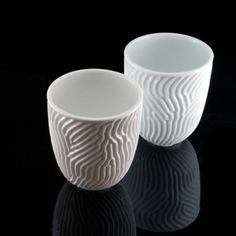 Holy unique coolness!    From the site:  Porcelain cups featuring an organic embossed surface. The form is the result of a computer simulation of reaction-diffusion, a natural patterning process that creates the dots and stripes seen on the skins and shells of many animals from tropical fish to zebras and leopards. The embossing creates a unique look as well as textural experience when handling the cup.    sold as a set of 4 or as a single cup. holds ~10 ounces.