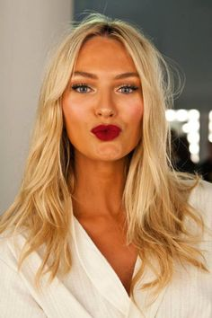 I love how dewy her skin is! Wonderful blush and highlighter, and that dark, matte red lipstick is to die for.