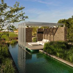 Pergola in a modern garden covering a seating place at the water side. Stone wall. GartenLandschaft Berg