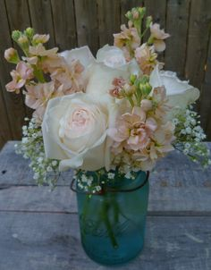 Vintage blue mason jars filled with OHara Roses, blush stock and baby's breath for an Oceanside wedding.  Designed by Paisley Floral Design Studio, Manchester NH