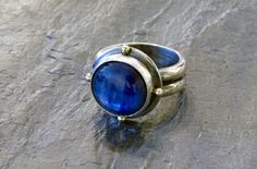 Beautiful, blue Kyanite! Kyanite brings trust, faith, patience, and respect.      - Bezel set in sterling silver with 18k gold      accents              – Gem quality kyanite  – Kyanite is 12mm in diameter