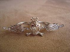 Anel em metal na cor prata em formato de caveira com tapa-olho e asas com aplicação de strass Swarovski branco.  Ambos os aros são 19 (diâmetro: 1,8cm) R$49,00