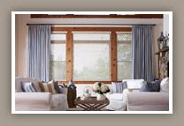 Large windows framed in colorful decorative drapes softens the view and brings this room together.  Budget Blinds of Boise