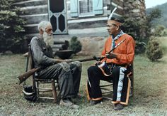 An Appalachian man converses with an Indian in front of a log cabin, 1939, Great Smoky Mountains National Park.