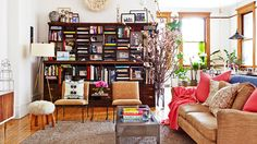 Home Tour: A Fashion Designer's Airy SoHo Loft // eclectic, modern, tripod lamp, bookcase, cherry blossom branches, living rooms