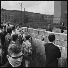 West Berliners looking over a portion of the Berlin Wall at the time of its construction. East German soldiers looking back, West Berlin, Germany, August 1961.