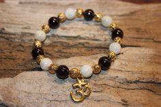 Bracelet ''Passion''  Bracelet fait de pierre semi-précieuse grenat et de perle d'eau douce avec ou sans insertion de couleur or  signe de ''Ohm''.
