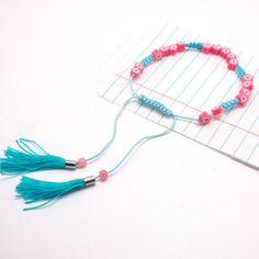Armband Hanna Neon pink und türkis, NOI home & fashion   Colour up you life - mit diesen farbenfrohen Armbändchen. Pinke Steinchen in Form eines Blümchen in Kombination mit dem kontrastfarbenen Bändchen machen es besonders. Es lässt sich in seiner Grösse verstellen und am Ende des Bändchens baumeln Mini-Troddeln.   Maße: Größe verstellbar  Material: Polyester mit Perlen #NOIhamburg #armband #troddeln #fashion #girlstyle #schmuck