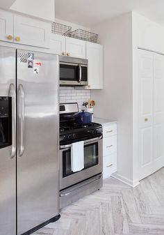 ... Refrigerator Situated Under White Cabinets Adorned With Schoolhouse  Electric Edgecliff Hex Knobs Placed Next To A Stainless Steel Stove And  Microwave ...
