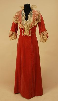 English Trained Rose Velvet Dinner Dress - One Piece, The Open Bodice With Four Sequin And Crystal Bead Flower Appliques, Embroidered Net Insert And Sequined Butterfly Applique, Elbow Length Sleeve Slit And Turned Back To Reveal Lace Lining And Puffed Inner Sleeve, Net Shawl Collar With Floral Embroidery, Pink Silk Lining And Pleated Hem Ruffle   c.1904