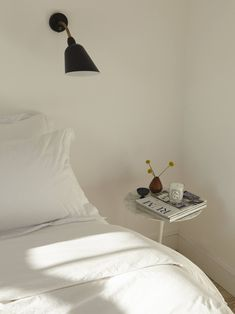 The bedside reading lights are Arne Jacobsen AJ9 Bellevue Wall Lamps by &Tradition.