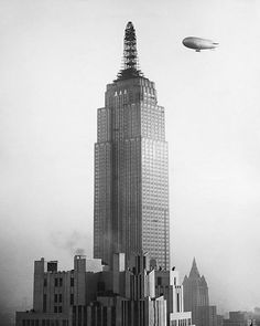 Blimp approaching Empire State Building under construction...the proposed mooring site which topped off the building was never used as such.