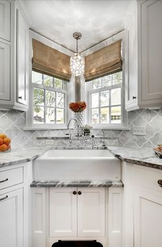Fabulous kitchen with corner farmhouse sink paired with gooseneck faucet below a pair of small windows dressed in woven shades illuminated by a capiz shell pendant. The white kitchen cabinets pair with oil-rubbed bronze hardware and gray marble counters below a gray arabesque backsplash. I have never seen a farmhouse sink in the corner like this.