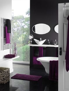 Give a sleek monochrome bathroom a hit of colour with stylish aubergine accessories and the bold use of animal print. Image by Matalan.