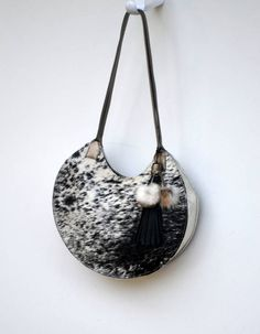 Fun new bag with salt & pepper hair-on cowhide and rabbit fur pompons in an elegant round shape. More photos and many more bags at alchemyleathergoods.etsy.com.  Each bag is one of a kind, designed and made by yours truly in my Alamo, California home studio.