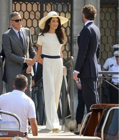 Amal Clooney wears a white and navy top with wide-leg trousers and an oversize straw hat