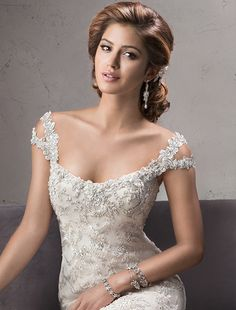 Maggie Sottero - MERCEDES, Elaborate patterned lace adorns this breathtaking tulle fit and flare wedding dress, complete with stunning illusion sweetheart neckline and illusion back. Finished with covered button over zipper closure. Tulle veil sold separately.