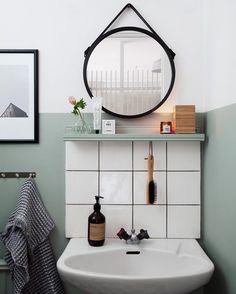 Salle de bains rétro avec sa crédence à grands carreaux et son miroir rond