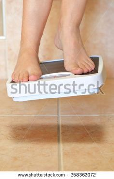 Woman's feet and bathroom scale hovers above the floor
