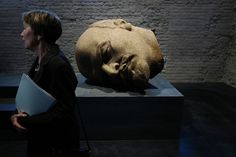 "Museum and project director Andrea Theissen stands next to the head of a 19-meter statue of former Soviet leader Vladimir Lenin at the permanent exhibition, ""Unveiled, Berlin and its Monuments,"" as she speaks to reporters in Berlin's Spandau Citadel Museum on April 27, 2016. The exhibition illustrates German history through the many monuments and memorials that have appeared in the capitol since the early 18th century."