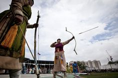 A Mongolian woman discharges an arrow from a bow at an archery competition during the Naadam Festival in Ulan Bator, Mongolia Wednesday, July 11, 2012. Mongolians celebrate the anniversary of Genghis Khan's march to world conquest on July 11 with the annual sports festival featuring traditional Mongolian events including wrestling, archery, and horse racing.