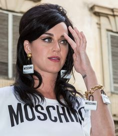 Katy Perry accessorized with dangling earrings and a gold bracelet