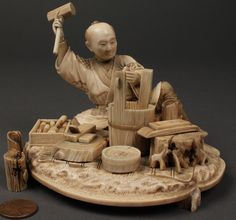 """Finely detailed carved ivory okimono of a seated man with various tools including hammer and plane. Inlaid mother of pearl panel on base with signature. Condition: one of the stump groupings formerly attached to the front right side ismissing; glue residue near man's foot indicates another possible loss; man's pouch detached from his obi (sash) in rear but retained. 3 3/4""""H x 5 1/2""""W x 4 1/2""""D. Japanese, Meiji period."""