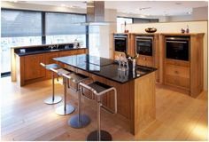 This display piece is from one of Britain\'s most exclusive Design Houses. It is manufactured from the highest quality clean-filled British Oak and has a Sutton Pearl Granite Worktop.     Included in the display is a run of tall units, a run of mid-height units a sink run and an island with attractive curved stools. £44000