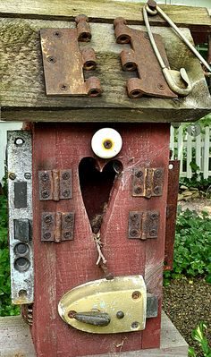 Rusty door hinges, a draw pull, a heavy door lock and a huge safety pin accessorize a bird house. This gardener also uses old license plates for roofs and a faucet for a perch on other bird houses.