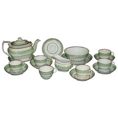 Lustre Tea Set  England  Circa 1800  Tea set with 17 pieces include teapot, undertray, creamer, cake plate, bowl, 6 saucers and 6 cups. Neo-classic design. White ground with green pattern and pink lustre border.