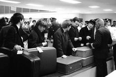 February 7 1964 The Beatles and Brian Epstein waiting for their luggage after arriving in New York for their first tour of America.