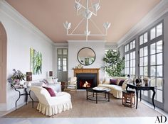 In this Seattle home revamped by Jeffrey Bilhuber, a ceiling coated in Farrow & Ball's Setting Plaster paint lends a blushing glow to the living room.