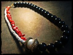 handmade necklace made of black glass stones, red coral chips, white round chaolitis stones, gold-plated bead caps