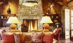 На фотографии показан интерьер гостиной в срубе. В комнате стены, потолок и пол деревянные. Деревянные доски не красили, чтоб была видна структуру дерева. В центре комнаты разместили мягкий диван, ...