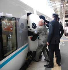 Only in Japan... trying to get the mascot into the train.