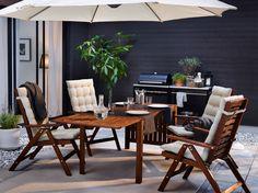Eine Terrasse mit ÄPPLARÖ Tisch und 4 Hochlehnern braun lasiert und HÅLLÖ Sitz- und Rückenpolstern in Beige
