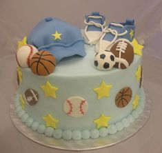 football and soccer, basketball and baseball balls, made from fondant, and placed near a pale blue baseball cap, and little pale blue sneakers, on top of a light turquoise cake, decorated with balls, and yellow stars