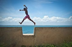 "24. ""The soul of the child."" A boy jumps over the recess in the 500-meter-high fortress wall. Morro de Sao Paulo, Bahia, Brazil. (Mauricio P..."