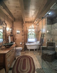 This rustic yet luxurious log home bathroom by Hochstetler Log Homes includes a relaxing soaking tub, glass walk-in shower, large vanity with vessel sink, and beautiful exposed beams. #loghomes #logcabins #loghomebathroom #rusticbathroom #exposedbeams