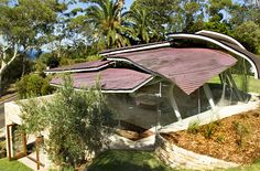 This lovely residence in Sydney, Australia is characterized by the crown of curvy copper panels that form its roof, resembling a pile of falling leaves.