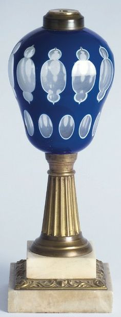 A Boston & Sandwich Glass Co, cut double overlay glass sperm or whale fluid lamp, 1860 to 1880, font cut in blue to white to clear with a row of combined slashes, punties and ovals over a row of ovals, above a fluted brass standard and stepped white marble base, Massachusetts